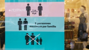 A sign showing the maximum number of clients is seen at the entrance of a clothing store in Montreal, on Wednesday, December 2, 2020. The Quebec government announced that stores will have to set the maximum capacity of customers based on floor space available to customers. THE CANADIAN PRESS/Paul Chiasson