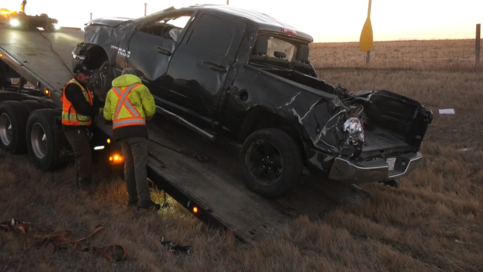 A damaged Dodge Ram truck being loaded onto a flatbed truck along the Trans-Canada Highway following a Friday morning crash west of Calgary city limits. The driver of the truck has not been located.