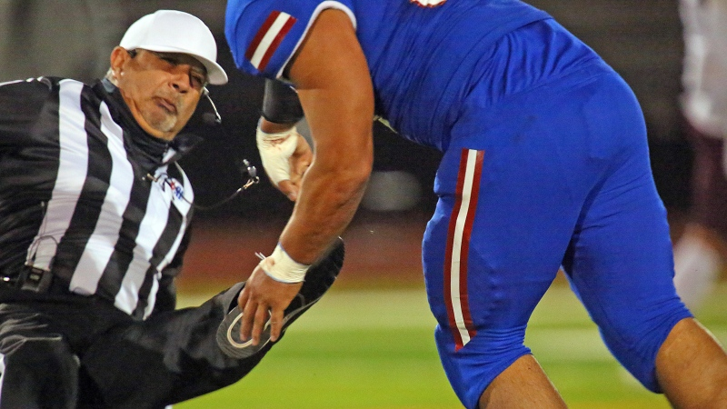 Football referee Fred Gracia falls to the turf after being charged by Edinburg's Emmanuel Duron in Edinburg's high school zone play-in game against Pharr-San Juan-Alamo on Thursday, Dec. 3, 2020, in Edinburg, Texas. Duron was escorted from the stadium by police officers. (Joel Martinez/The Monitor via AP)