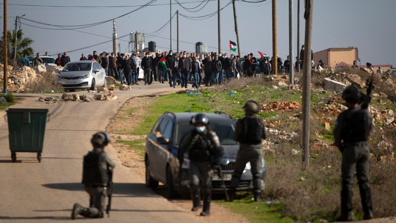 Israeli border police officers and Palestinians clash during a protest against the expansion of Israeli Jewish settlements near the West Bank town of Salfit, Thursday, Dec. 3, 2020. (AP Photo/Majdi Mohammed)
