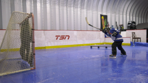 Ashton Schenk, 8, playing hockey on a backyard rink his dad Dean constructed in their shed. (Claire Hanna/CTV News)