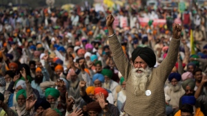 An elderly farmer shouts slogans as others listen to a speaker as they block a major highway during a protest to abolish new farming laws they say will result in exploitation by corporations, eventually rendering them landless, at the Delhi-Haryana state border, India, Tuesday, Dec. 1, 2020. (AP / Altaf Qadri)
