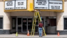 Two men work on the marquee of an independent theatre in Ottawa, Wednesday, May 6, 2020. THE CANADIAN PRESS/Adrian Wyld