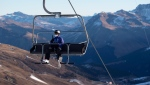 In this Sunday, Nov. 29, 2020 file photo a ski enthusiast wearing a protective face mask takes a chair lift in Arosa, Switzerland. (Gian Ehrenzeller/Keystone via AP, File)