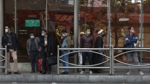 People wearing face masks to help prevent the spread of the coronavirus wait at a bus stop in downtown Tehran, Iran, Saturday, Dec. 5, 2020. (AP Photo/Vahid Salemi)
