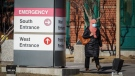 A woman wearing a mask walks past the Peter Lougheed Hospital in Calgary, Alta., Thursday, Dec. 3, 2020, amid a worldwide COVID-19 pandemic. THE CANADIAN PRESS/Jeff McIntosh