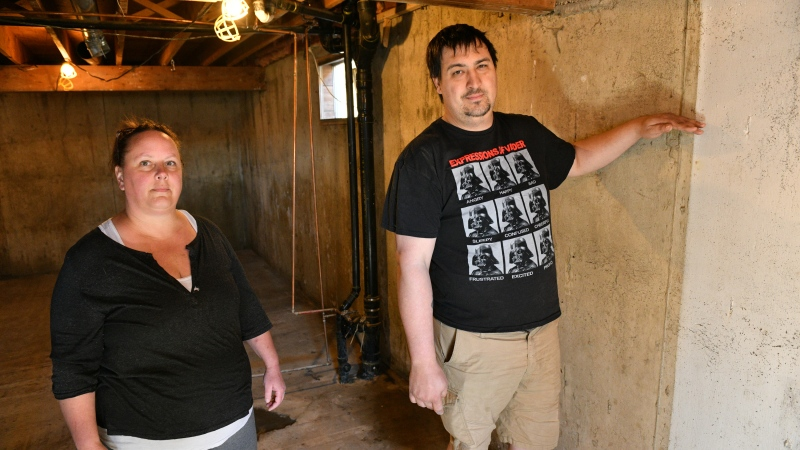 Homeowners Cora and Alec Dion pose in the basement of their home in Fort McMurray, Alta., on May 8, 2020. The Dions had about five feet of water in their basement as a result of recent flooding in downtown Fort McMurray. This marked the second time the couple faced evacuation from their home since the Horse River wild fire of May 3, 2016. THE CANADIAN PRESS/Greg Halinda