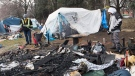 A man looks on as workers remove debris following a fire in a tent at a homeless camp in Montreal, Saturday, Nov. 5, 2020.The COVID-19 pandemic continues in Canada and around the world. THE CANADIAN PRESS/Graham Hughes