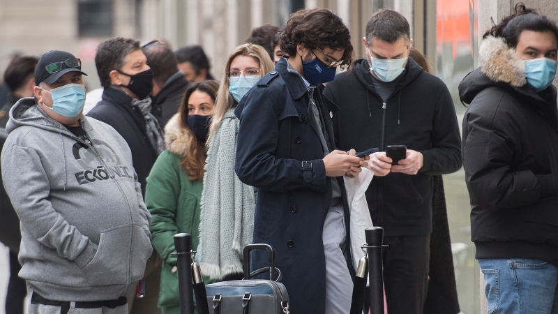 People wear face masks as they wait to enter a store in Montreal, Saturday, December 5, 2020, as the COVID-19 pandemic continues in Canada and around the world. THE CANADIAN PRESS/Graham Hughes