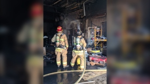 Firefighters extinguish a blaze in a garage at 426 Gladstone Avenue in Ottawa's Centretown neighbourhood. (Photo courtesy: Twitter/OFSFirePhoto)