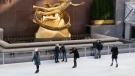 People wearing masks skate beneath a statue of Prometheus, also with a mask, at Rockefeller Center, Thursday, Dec. 3, 2020 in New York. What's normally a chaotic, crowded tourist hotspot during the holiday season is instead a mask-mandated, time-limited, socially distanced locale due to the coronavirus pandemic. (AP Photo/Mark Lennihan)