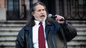 Mark Donnelly, who has been the anthem singer for the Vancouver Canucks NHL hockey team since 2001, performs O Canada at a protest against measures taken by public health authorities to curb the spread of COVID-19, in Vancouver, B.C., Saturday, Dec. 5, 2020. THE CANADIAN PRESS/Darryl Dyck