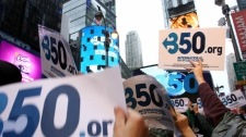 Signs are raised by participants in an International Day of Climate Action rally in New York on Saturday, Oct. 24, 2009. (AP / Tina Fineberg)