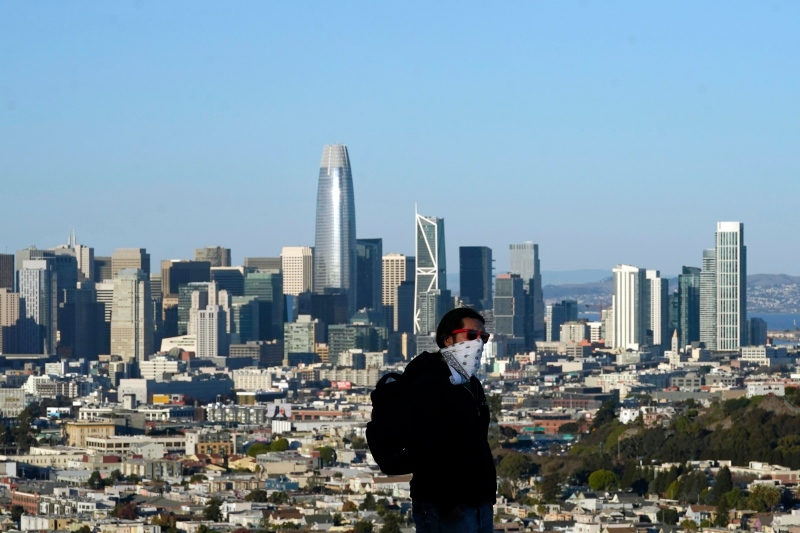 A person wearing a protective mask walks in front of the skyline on Bernal Heights Hill amid the coronavirus pandemic in San Francisco, Monday, Dec. 7, 2020. (AP Photo/Jeff Chiu)