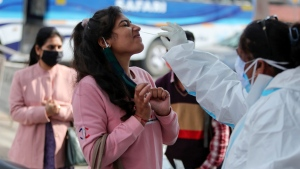 A woman reacts as a health worker collects a swab sample to test for COVID-19 by a road side in Jammu, India, Monday, Dec.7, 2020. India is second behind the U.S. in total coronavirus cases but has one of the lowest deaths per million population globally. (AP Photo/Channi Anand)