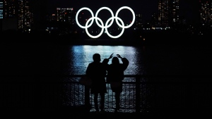 In this Dec. 1, 2020, file photo, a man and a woman look at the Olympic rings float in the water in the Odaiba section in Tokyo. (AP Photo/Eugene Hoshiko, File)