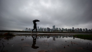 A person carrying an umbrella is silhouetted against the downtown skyline while walking on the seawall in Stanley Park, in Vancouver, on Wednesday, Dec. 9, 2020. (Darryl DyckTHE CANADIAN PRESS)