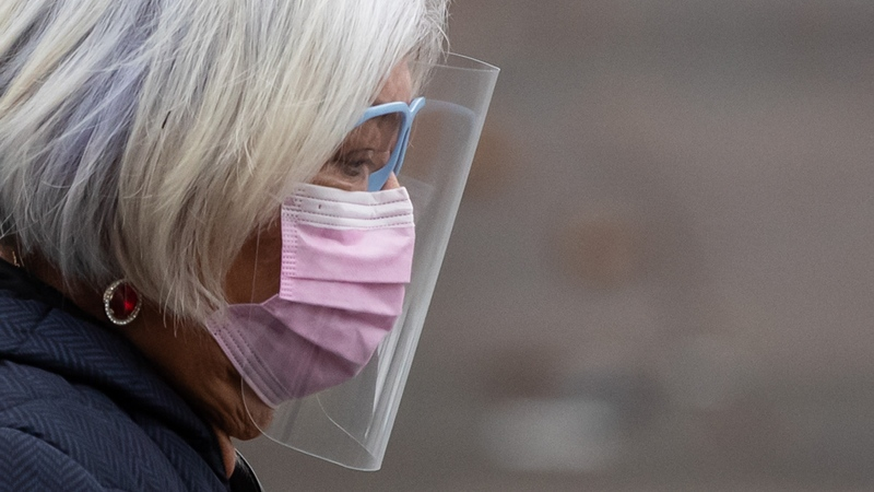 A person wears a face mask and shield to curb the spread of COVID-19 while walking in Vancouver on Sunday, Dec. 6, 2020. (Darryl Dyck / THE CANADIAN PRESS)