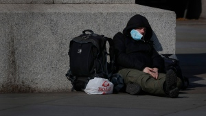 A man sleeps on the pavement in Westminster in London, British people have been told to stay home to prevent the spread of the new coronavirus, Friday, March 27, 2020. Local Authorities in England have been asked by the prime minister's homelessness advisor to house all homeless people by the weekend, to help stop the spread of COVID-19. (AP Photo/Frank Augstein)