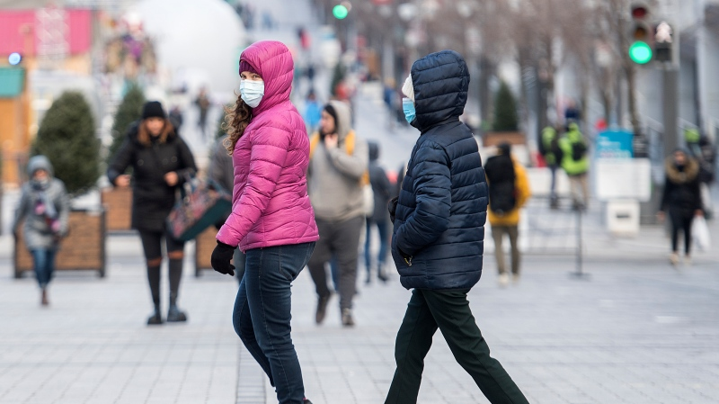 People wear face masks as they walk along a street in Montreal, Saturday, December 5, 2020, as the COVID-19 pandemic continues in Canada and around the world. THE CANADIAN PRESS/Graham Hughes