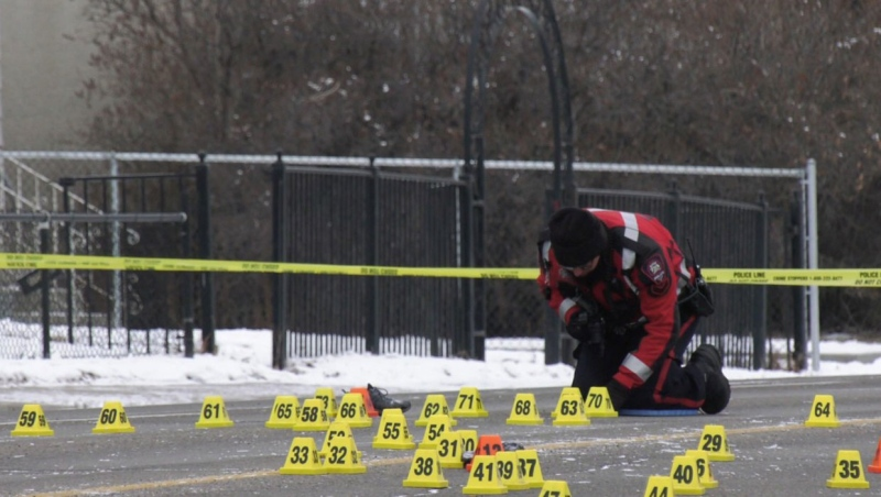 A CPS member kneels next to evidence markers near the intersection of 37 St and 13 Ave SW follwing a hit-and-run on Dec. 13, 2020. (file)