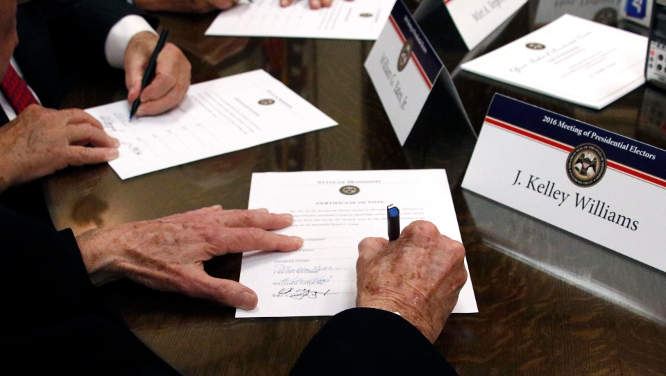 In this Dec. 19, 2016, file photo members of the Mississippi Electoral College sign certificates of vote in the process of formally casting their electoral votes in the 2016 General Election for President and Vice President of the United States at the Capitol in Jackson, Miss. (AP Photo/Rogelio V. Solis, File)