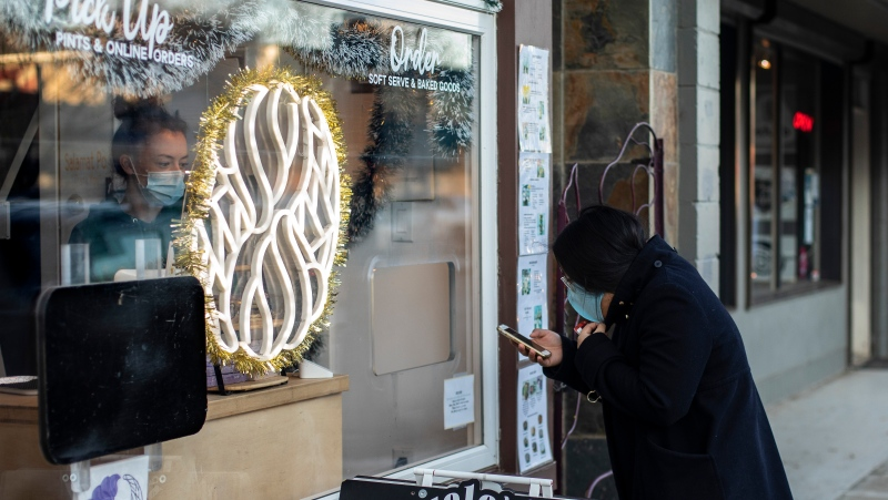 A customer makes an order through a window in Edmonton on Saturday, December 12, 2020. New COVID-19 measures mean businesses will be required to close, reduce capacity or limit their in-person access as well as no large gatherings. THE CANADIAN PRESS/Jason Franson