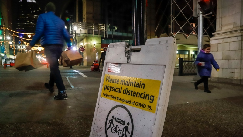 Pedestrians walk past a physical distancing sign in Calgary, Alta., Saturday, Dec. 12, 2020, amid a worldwide COVID-19 pandemic. THE CANADIAN PRESS/Jeff McIntosh
