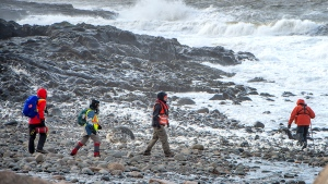Members of a ground search and rescue team walk along the shore of the Bay of Fundy in Hillsburn, N.S. in an area where empty life-rafts from a scallop fishing vessel where reported on Tuesday, Dec. 15, 2020. Search and rescue aircraft, along with Canadian Coast Guard boats have been dispatched as well. (THE CANADIAN PRESS/Andrew Vaughan)