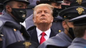 Surrounded by Army cadets, U.S. President Donald Trump watches the first half of the 121st Army-Navy Football Game in Michie Stadium at the United States Military Academy, Saturday, Dec. 12, 2020, in West Point, N.Y. (AP Photo/Andrew Harnik)