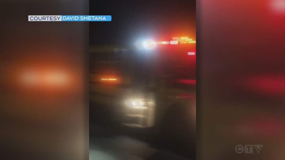 Truck passes school bus with red lights flashing