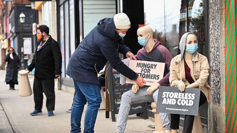 Jacob Gawrysiak adjusts a sign on mannequin with key messages displayed in doorways of select small business pleading for action to support local businesses during the COVID-19 pandemic in Toronto on Tuesday, December 15, 2020. THE CANADIAN PRESS/Nathan Denette