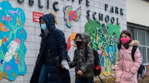 A family walk past the sign at Thorncliffe Park Public School in Toronto on Friday December 4, 2020. Toronto Public Health closed the school due to a COVID19 outbreak. THE CANADIAN PRESS/Frank Gunn