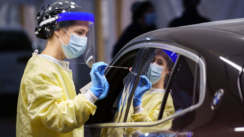 FILE - A nurse performs a test on a patient at a drive-in COVID-19 clinic in Montreal, on Wednesday, October 21, 2020. THE CANADIAN PRESS/Paul Chiasson