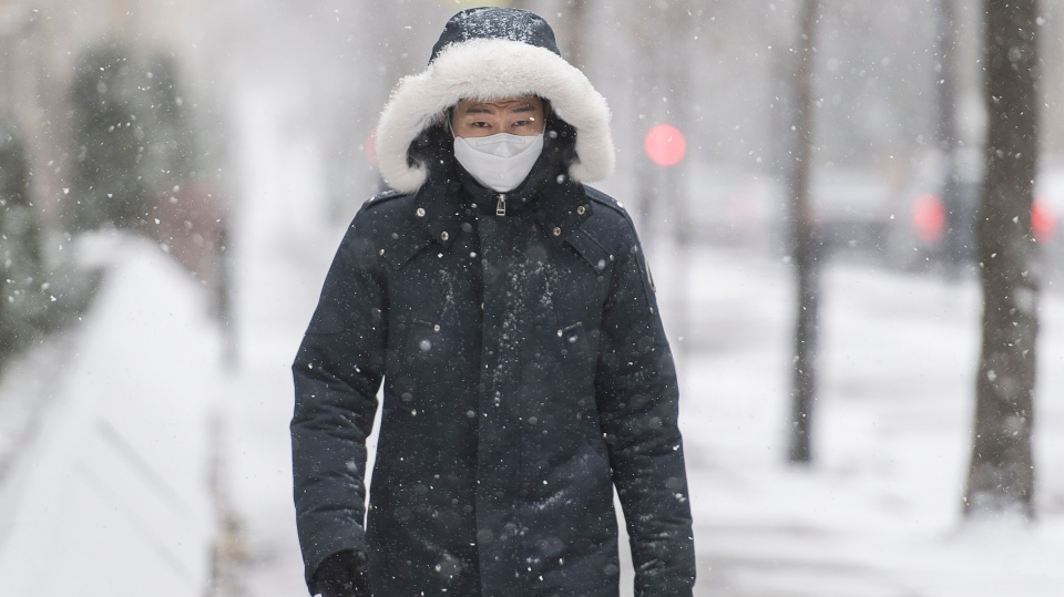 A man wears a face mask as he walks along a street during light snowfall in Montreal, Sunday, December 20, 2020 as the COVID-19 pandemic continues in Canada and around the world. THE CANADIAN PRESS/Graham Hughes