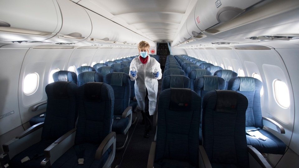 A flight attendant wears personal protective equipment as they walk through the back part of a near empty plane travelling from Calgary to Vancouver, Tuesday, June 9, 2020. THE CANADIAN PRESS/Jonathan Hayward
