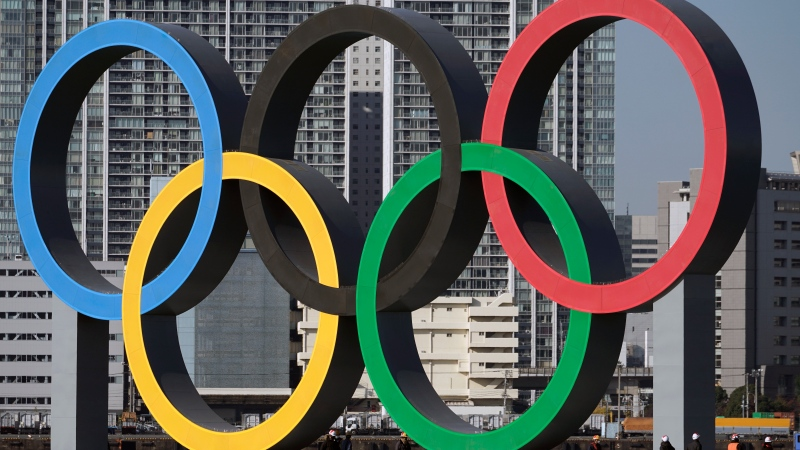 FILE - In this Dec. 1, 2020, file photo, the Olympic Symbol is reinstalled after it was taken down for maintenance ahead of the postponed Tokyo 2020 Olympics in the Odaiba section, in Tokyo. (AP Photo/Eugene Hoshiko, File)