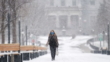 A woman wears a face mask as she walks through McGill University during light snowfall in Montreal, Sunday, December 20, 2020 as the COVID-19 pandemic continues in Canada and around the world. THE CANADIAN PRESS/Graham Hughes