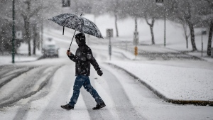Heavy snow falls as a person wearing a face mask to curb the spread of COVID-19 carries an umbrella while crossing a road in Burnaby, B.C., on Monday, December 21, 2020. Environment Canada issued a snowfall warning on the first day of winter with up to 5cm of snow expected for Metro Vancouver and up to 20cm for other areas of the province. THE CANADIAN PRESS/Darryl Dyck