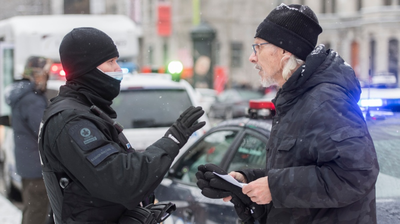 A man talks with a police officer after being issued a fine during a demonstration in Montreal, Sunday, December 20, 2020. THE CANADIAN PRESS/Graham Hughes