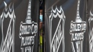 """A security guard peers out from behind NHL branded fencing at the entrance where players arrive at Toronto's Royal York hotel, part of the NHL """"bubble"""" in Toronto, Sunday, July 26, 2020. THE CANADIAN PRESS/Chris Young"""