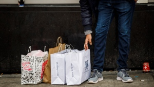 A man checks his shopping bags while he smokes a cigarette outside Toronto Eaton Centre during Boxing Day in Toronto, Thursday, Dec. 26, 2019. (THE CANADIAN PRESS/Cole Burston)