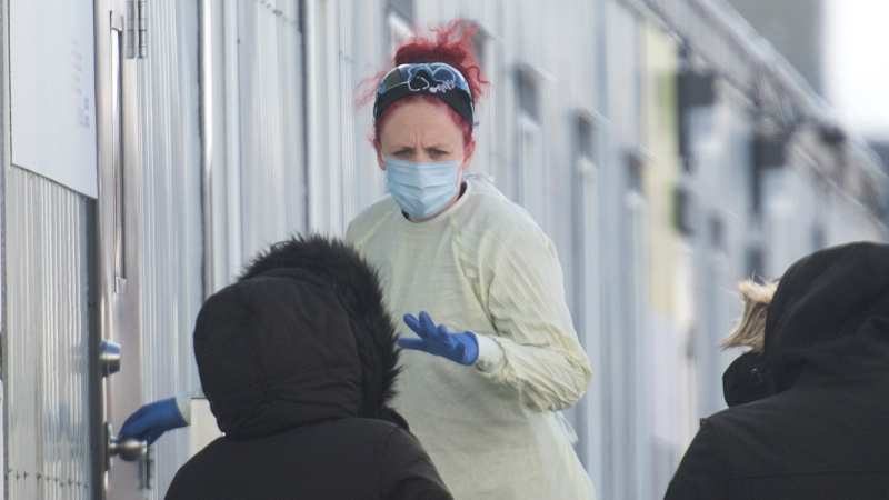 A health-care worker talks with people as they wait to be tested for COVID-19 at a clinic in Montreal, Sunday, Dec. 27, 2020, as the COVID-19 pandemic continues in Canada and around the world. THE CANADIAN PRESS/Graham Hughes