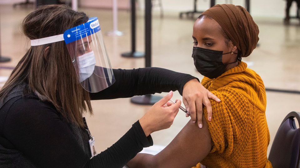 A nurse gives the first COVID-19 vaccine in Edmonton, to Sahra Kaahiye in Edmonton on Tuesday, December 15, 2020. THE CANADIAN PRESS/Jason Franson