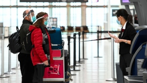 People wearing protective equipment check in at the international departures at Pearson International Airport during the COVID-19 pandemic in Toronto on Monday, December 14, 2020. International travellers will now have to pay for a COVID-19 test if required. THE CANADIAN PRESS/Nathan Denette