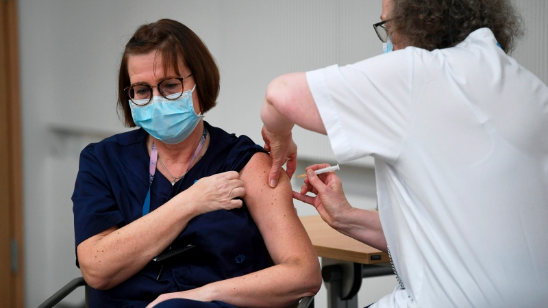Nurse Eija Koponen receives a Pfizer BioNTech COVID-19 vaccination, at the Helsinki University Hospital in Helsinki, Finland, Saturday, Dec. 27, 2020. (Antti Aimo-Koivisto/Lehtikuva via AP)