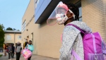 Five year-old Nancy Murphy wears a full mask and face shield as she waits in line for her kindergarten class to enter the school at Portage Trail Community School which is part of the Toronto District School Board (TDSB) during the COVID-19 pandemic in Toronto on Tuesday, September 15, 2020. THE CANADIAN PRESS/Nathan Denette