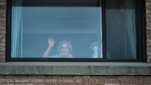 Alicia Tamayo, left, 95, waves to her daughter Betty Fernandez from her window at the Eatonville Care Centre where multiple deaths from COVID-19 has occurred in Toronto on Tuesday, April 14, 2020. Health officials and the government have asked that people stay inside to help curb the spread of COVID-19. THE CANADIAN PRESS/Nathan Denette