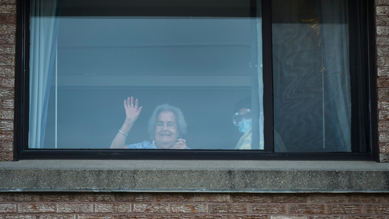 Alicia Tamayo, left, 95, waves to her daughter Betty Fernandez from her window at the Eatonville Care Centre where multiple deaths from COVID-19 have occurred in Toronto on Tuesday, April 14, 2020. THE CANADIAN PRESS/Nathan Denette