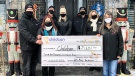 The Vanleeuwen family presents a cheque to Childcan in Ilderton, Ont. on Thursday, Dec. 31, 2020. (Jim Knight / CTV News)